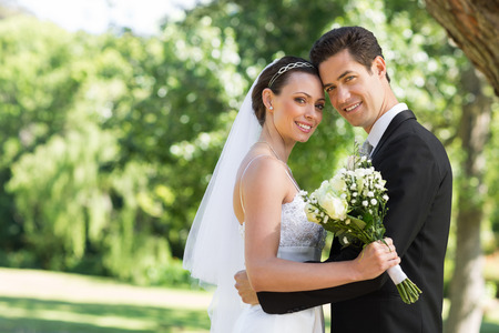 Portrait of loving newly wed couple with head to head standing in garden Stock Photo