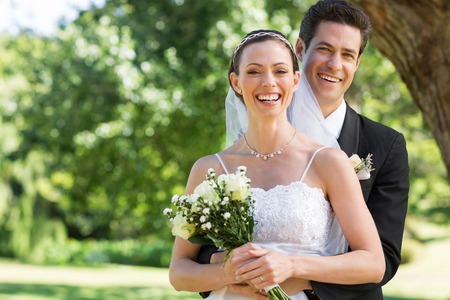 Portrait of newly wed couple with flower bouquet in park photo
