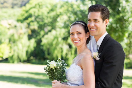 wedding gown: Happy loving newly wed couple looking away while standing in park Stock Photo