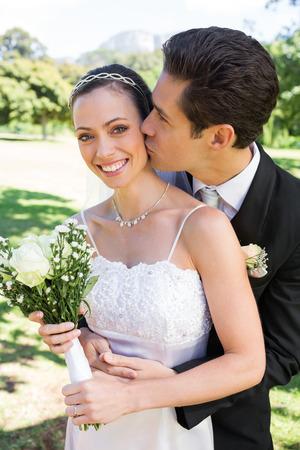 Young groom kissing happy bride on cheek in garden photo