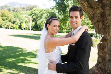 Portrait of smiling young bride and groom embracing in garden