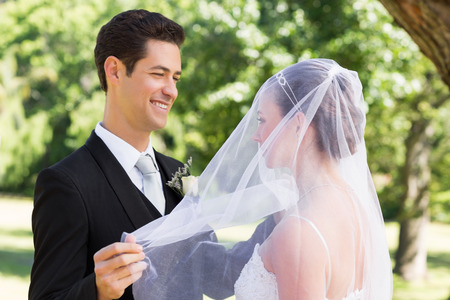 unveiling: Happy young groom unveiling his bride in garden