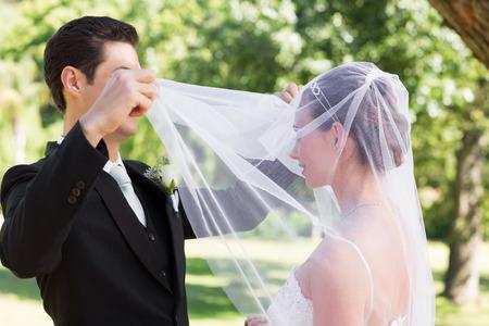 Young loving groom unveiling bride in garden photo