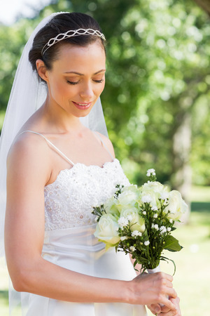 Beautiful shy bride holding flower bouquet in garden  photo