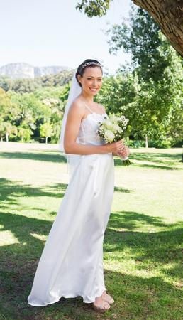 Full length portrait of confident bride holding flower bouquet in garden photo