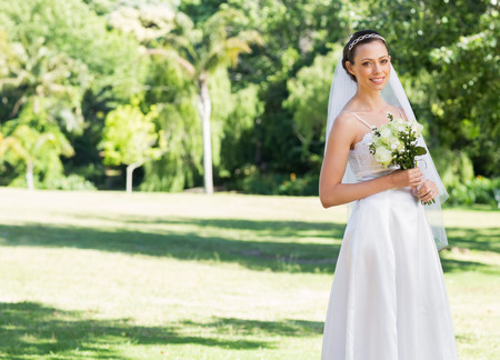 Attractive smiling bride holding flowers while standing in park photo