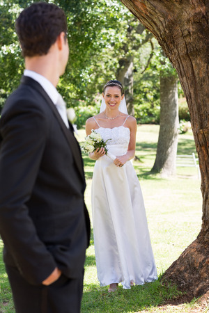 Happy bride holding bouquet while looking at groom in garden photo