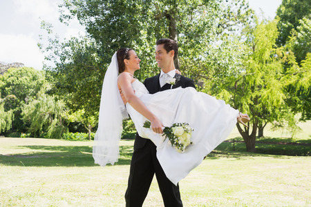 Young groom carrying bride in arms at garden photo