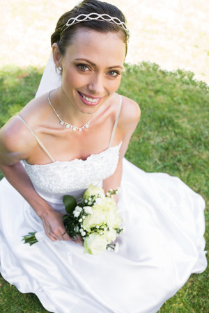 High angle portrait of beautiful bride holding flower bouquet while sitting on grass in garden photo