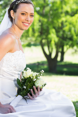 Portrait of beautiful bride holding flower bouquet while sitting in garden photo