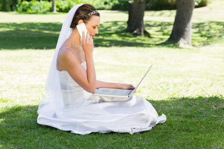 Side view of young bride using laptop and mobile phone while sitting on grass in park photo
