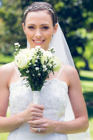 Portrait of an attractive bride smiling while holding flower bouquet in garden photo