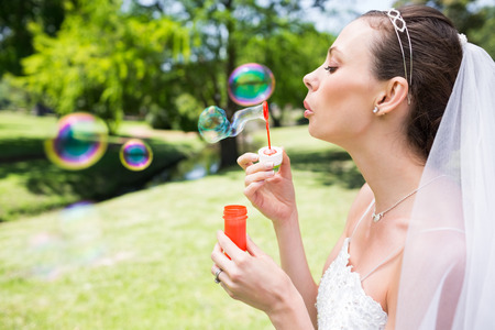 Closeup of beautiful bride blowing bubbles in garden photo