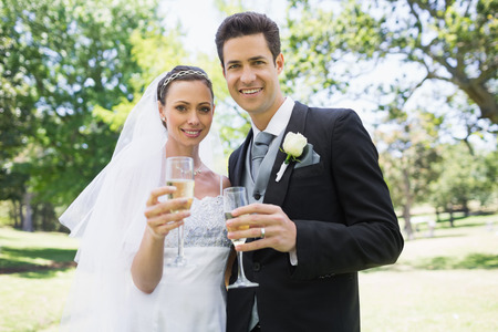 Portrait of newlywed couple toasting champagne in park photo