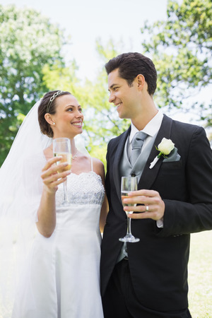 Romantic bride and groom having champagne while looking at each other in park photo