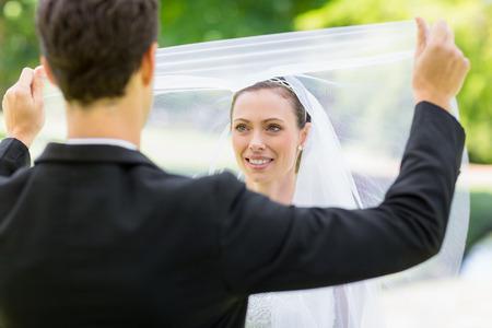 unveiling: Young groom unveiling his bride in garden