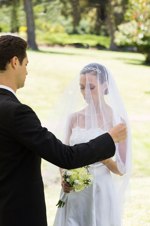 Young groom about to lift veil of bride in garden photo