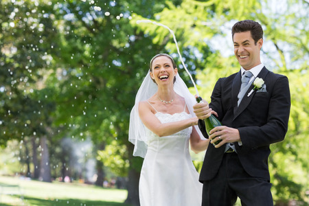 Young newlywed couple popping cork of champagne in park photo