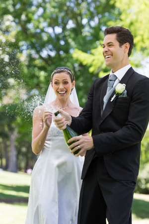 popping the cork: Young newlywed couple popping cork of champagne in park