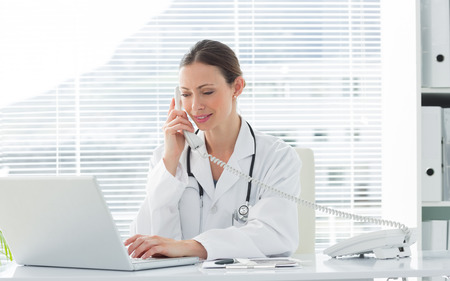 Beautiful female doctor talking on land line phone while using laptop at desk in clinic photo
