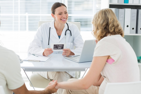 Happy female gynaecologist talking to expectant couple in clinic Stock Photo