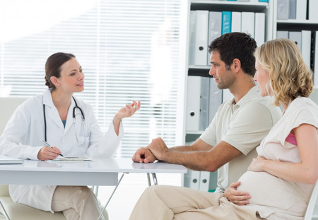 gynaecologist: Female gynaecologist discussing with expectant couple in clinic
