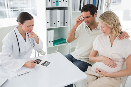 Expectant couple and female doctor discussing over reports in clinic