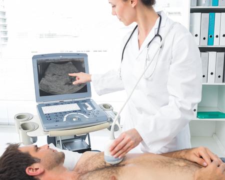 sonograma: Cardi�logo femenina mediante ecograf�a en el paciente var�n en la sala de examen