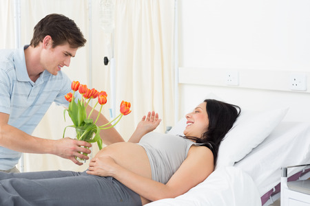 Young man offering flowers to pregnant woman lying in bed in hospital photo