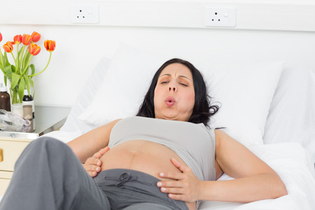 attractive pregnant: Pregnant woman suffering from labor pains lying in bed at hospital