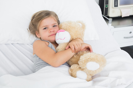 sick teddy bear: High angle portrait of cute girl embracing teddy bear while lying in hospital bed