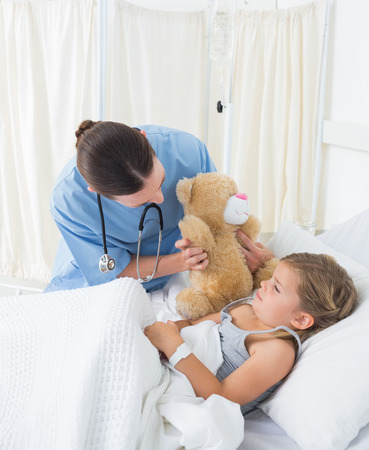 Female doctor with teddy bear entertaining sick girl in hospital bed photo