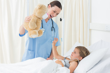 Playful female doctor entertaining sick girl with teddy bear in hospital bed photo