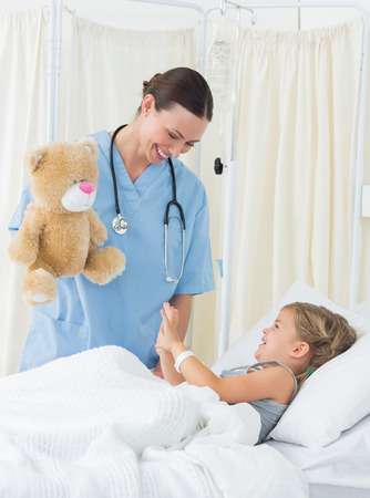 attend: Playful female doctor entertaining sick girl with teddy bear in hospital bed