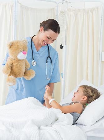 ragazza malata: Playful medico femminile divertente ragazza malata con orsacchiotto in letto d'ospedale