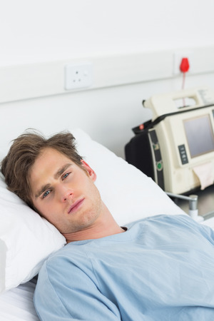Portrait of young male sick man lying in hospital bed photo