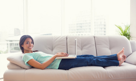 Young girl lying on sofa using her laptop smiling at camera at home in the living room photo