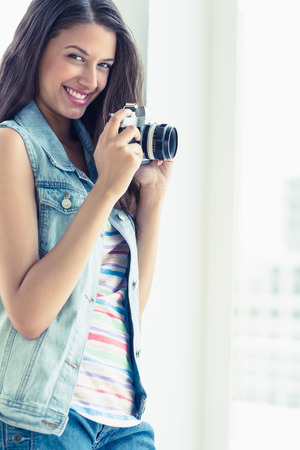 Stylish young woman taking a photo smiling at camera in a bright room photo