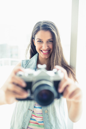 Smiling young woman taking a photo at camera in a bright room photo
