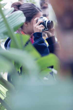 Young woman taking a picture in a wooded area on a sunny day photo