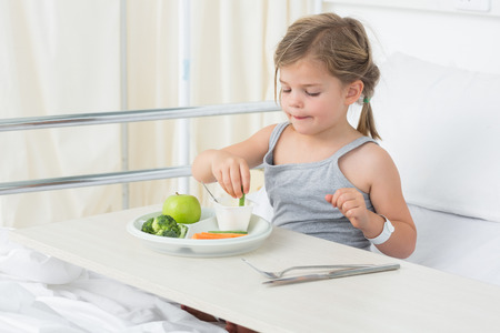 Little girl having healthy food in hospital bed photo