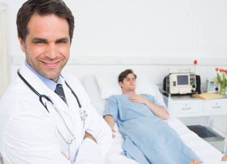 Portrait of confident male doctor in hospital with patient lying on bed in background photo