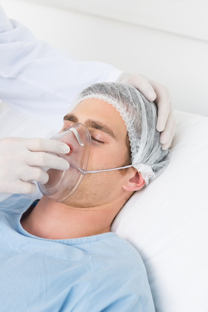 Cropped image of doctor adjusting oxygen mask on male patient in hospital ward photo