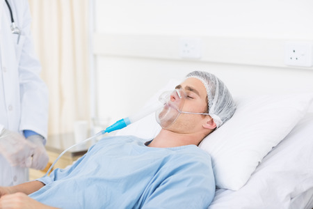 hospital gown: Midsection of doctor adjusting oxygen mask on patient in hospital ward