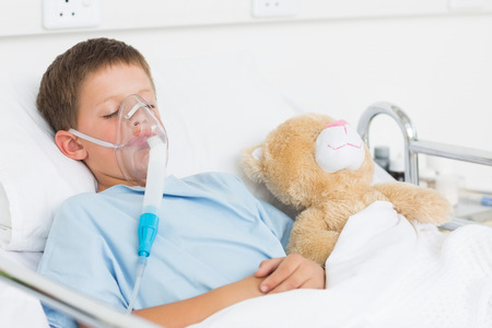 sick teddy bear: Sick boy wearing oxygen mask sleeping beside teddy bear in hospital bed Stock Photo