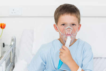 Portrait of sick little boy wearing oxygen mask in hospital bed photo