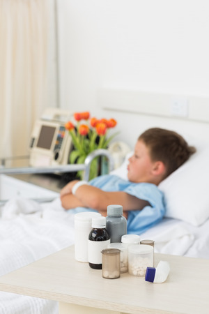 Focus on medicines on table with sick little boy in hospital bed photo