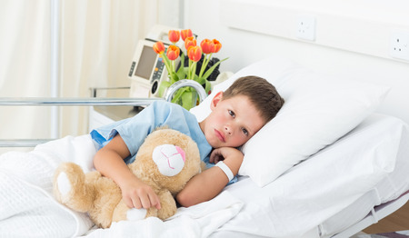 Portrait of sad boy lying with teddy bear in hospital bed photo