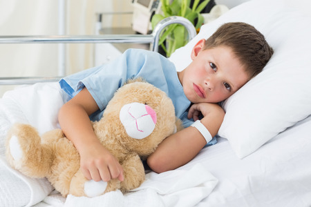 Portrait of sick little boy with teddy bear in hospital bed photo