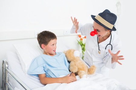 Female doctor in clown costume entertaining ill boy in hospital bed photo